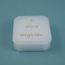 A curl box, inscribed 'A Wisp of Baby's Hair'.