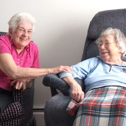 Pat Olsen left, shares a chuckle with Edythe Tomon on right. Pat helps in care for Edythe.