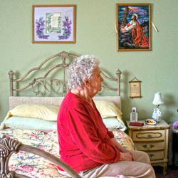 Marie Waage poses with some of her paintings that adorn her bedroom wall.