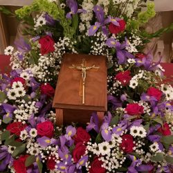 Cremation casket with cross and flowers at funeral.