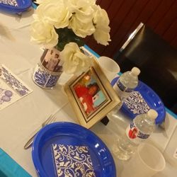 Guest table featuring personalized centerpiece vases, picture frames and water bottles