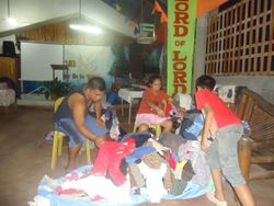 Pastor Jonathan and Pastora Gema sort the clothes to be distributed.