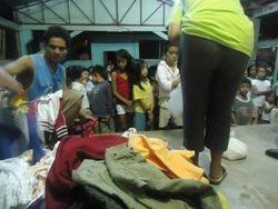 Pastora Gema distributes clothing to the children