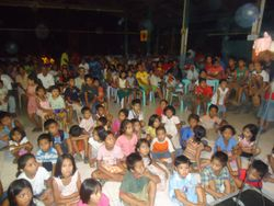 The children wait for the clothing to be distributed