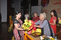 Dr. Jyotsna Gupta being presented with bouquet of flowers