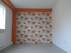 Dormitor cu tapet bej cu aspect floral orange