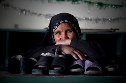 Afghan woman working as a mosque shoe keeper.