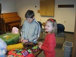 brother & sister making prayer dolls