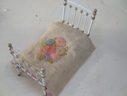 Old 1930s faded embroidery on very worn hessian makes a cottage- style bed cover.