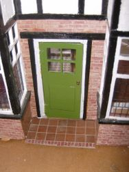 The front door has been changed from yellow to green and given a nicer handle than the screw that it had before/