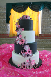 Four tier black and white wedding cake with cherry pink and violet fondant flowers.