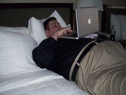 John Koch checking tournament schedule on the bed