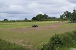 Cutting turf in a field beside the railway