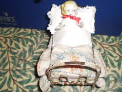 Bisque Doll in Antique Metal Bed