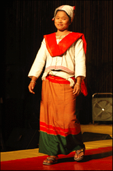 Gandabi Tanchangya is wearing a traditional Tanchangya five piece multicolored outfit.