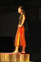 Rumi Tanchangya is wearing an A line skirt made with a Tanchangya pinon. Her top is woven black fabric with a scoop neck and criss-crossing laces along the side.