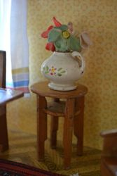 Old treen vase with cloth flowers on a nice round table