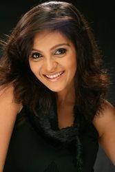 Ami Trivedi in black smiling
