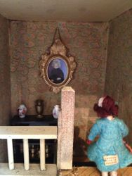 A large portrait of Cedric's first wife dominates the stairway.
