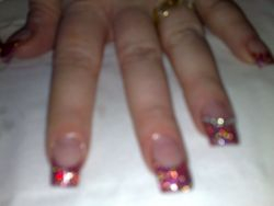 rainbow red acrylic nails with silver gems on ring finger