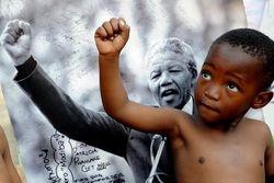 A child mimics Mandela's upright fist