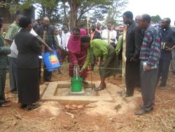 Bishop Mdegella assists a local woman as she draws the first water from the Pommern Water Project at the dedication ceremony