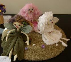 Three knitted fairies on grass by Janneke Engelbrecht