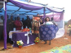 Mimi and Eric are given gifts of fabric by Bishop Mdegella