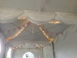 Marquee with white drapes, bunting and fairy lights