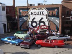 Members and their cars gather in front of Rt66 mural
