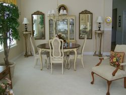 PROVINCIAL DISTRESSED LOOK DESIGNER DINING ROOM SET WITH CHINA CABINET, PROVINCIAL SET OF TALL PILLAR STANDS, MIRRORS, ANTIQUE HAND PAINTED LAMPS, WHITE UPHOLSTERED OCCASIONAL CHAIR, ANTIQUE PORCELAIN CHINA, ETCHED DEPRESSION GLASS, CUT CRYSTAL