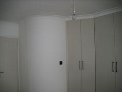 En-suite behind circular wall and end pair of wardrobe doors.