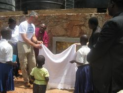 Unveiling the plaque on the water tank platform.  Bishop Mdegella and Eric held the cloth on the left while Pastor Sagga and Mimi held it on the right