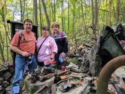 Jeff, Debbie, and Diana Mooney posing at the Flight 371 Memorial Plaque and surrounding debris.