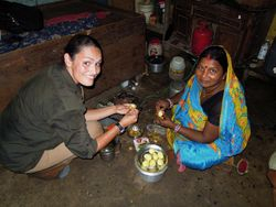 34 Lila Devi, Vijay's mother, prepares dinner for the family.  She has a one ring gas stove, no windows, and no running water.  'You find things to smile about.  I'm very proud of my son.'