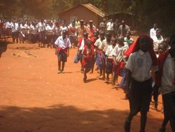The procession moves up the road past the Health Clinic.  Secondary School students (burgundy skirts or slacks) follow the Primary School students (blue skirts or shorts and red sweaters)