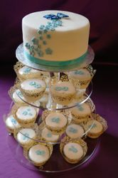 blue flower wedding cake with cupcakes