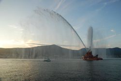 The Pobra festival - a boat carries a wreath out to sea as the rescue boat sprays water in the air