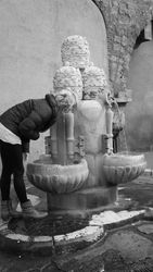 Woman drinking from a fountain, Rome