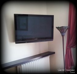"Wall mounted 58"" Flat screen TV on a swiveling arm"