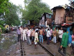 31 Sanjay Camp slum, Delhi, Vijay's home.  People stand back into doorways when they hear a train coming