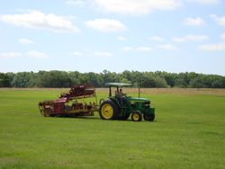 Tractor with roll harvestor attached