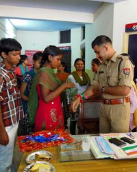 26 Street children tie friendship bracelets known as 'rakhis' on the police officers at Hari Parwat station, Agra.  The hope is to improve police treatment of street kids