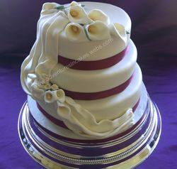 3 tier wedding cake with lilies icing swag and burgangy ribbon