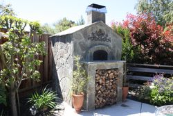 Wood burning pizza oven with flagstone facia and roof