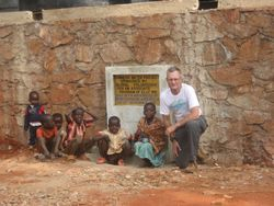 Eric with several local children by the Pommern Water Project plaque