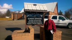 pastor Lincoln-proudly standing outside the church building after the installation service