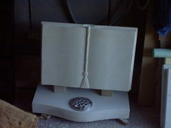 Portland stone cord & tassel book with tick rests and bow fronted base