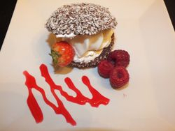 ice cream, chocolate and  coconut oyster shell dessert with fruit and raspberry sauce.