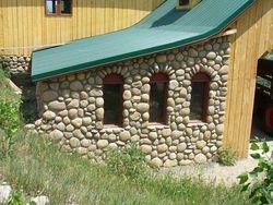River rock Barn at Lonehawk Farm with wagon wheel windows Longmont Boulder Colorado